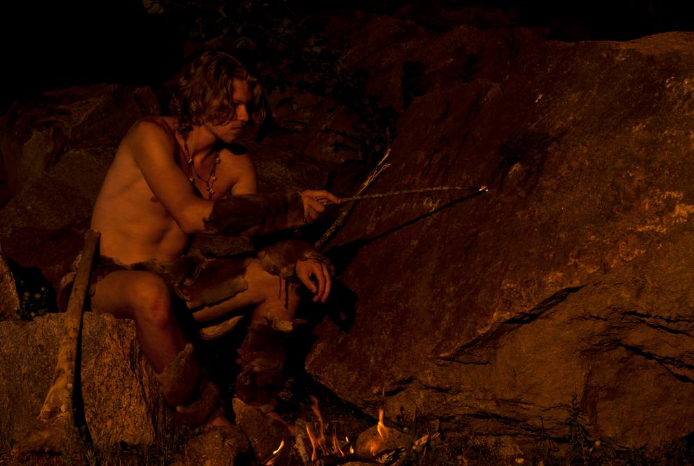 Homem primitivo dentro de uma caverna, escrevendo nas paredes
