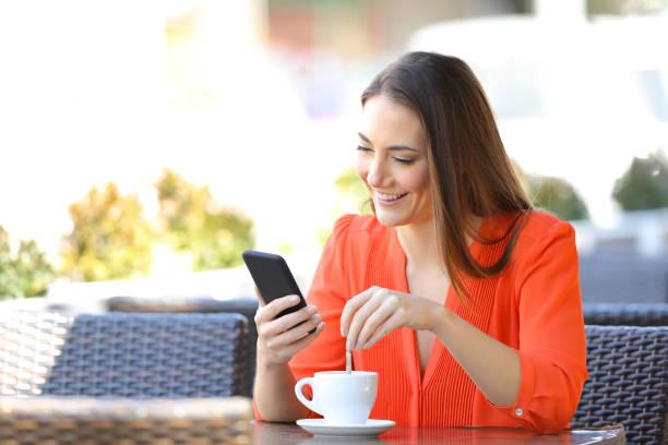 Mulher feliz utilizando telefone numa cafeteria