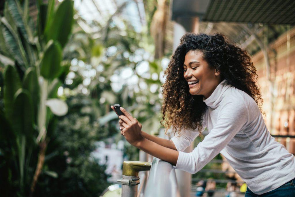 Mulher do cabelo cacheado apoiada em um corrimão, sorrindo para o celular. Plantas no fundo.
