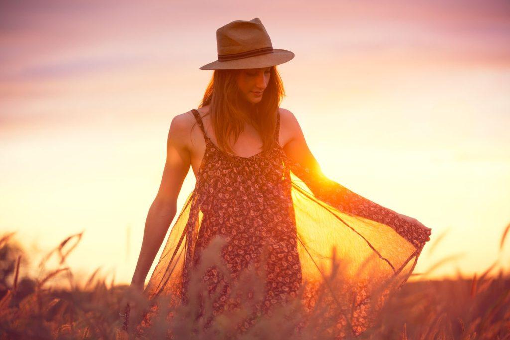 Mulher branca de chapéu balançando o vestido em um jardim durante o entardecer.