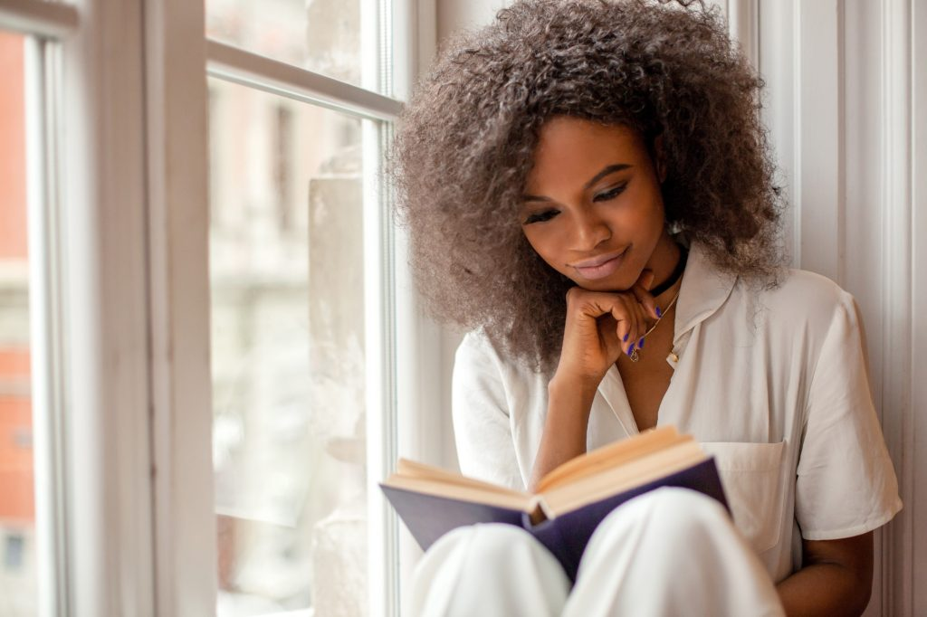 Mulher negra encostada na janela lendo um livro.