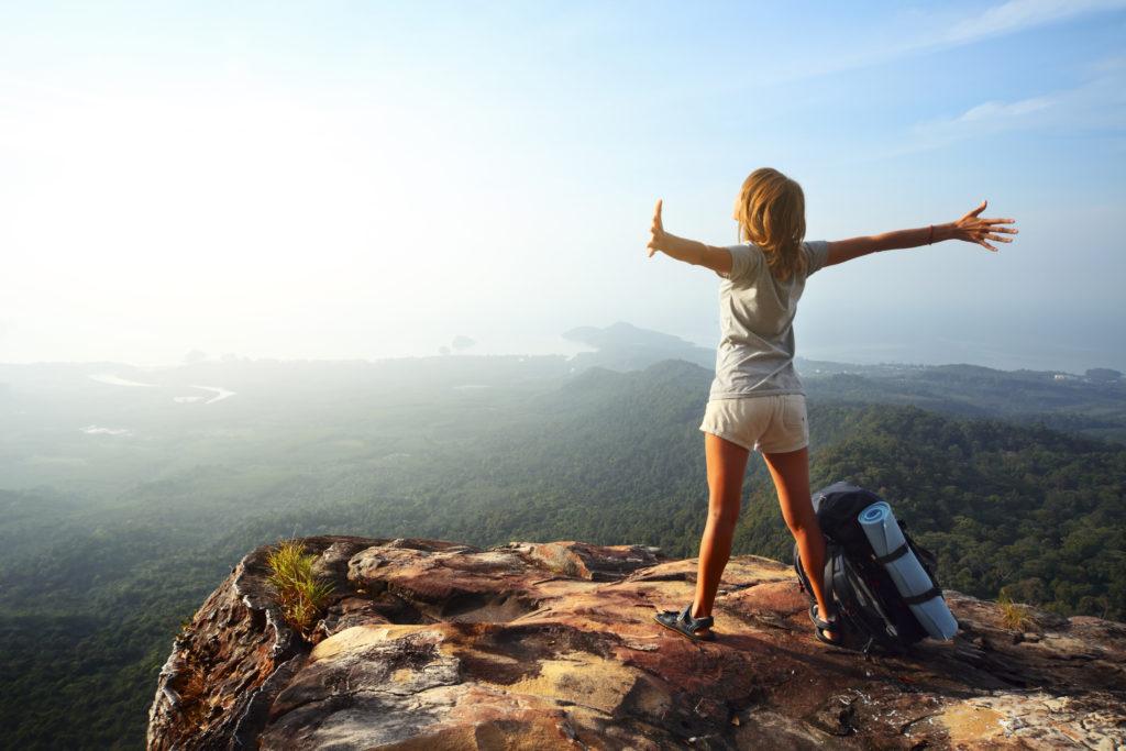 mulher plena e realizada encima de uma montanha