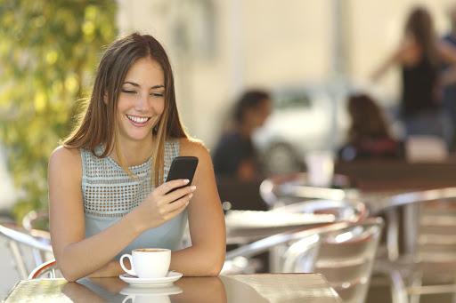 mulher tomando cafe vendo o telefone